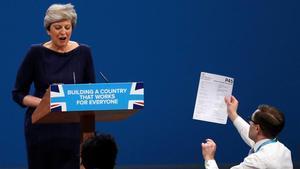 Un espontáneo entrega una hoja de despido a la primera ministra británica, Theresa May, durante su discurso de clausura de la conferencia del Partido Conservador en Manchester.