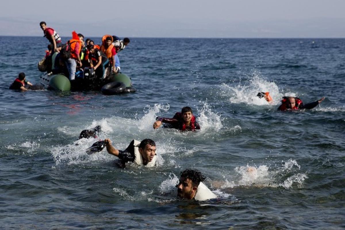 Inmigrantes tratan de subir a un bote, cerca de la isla griega de Lesbos, el pasado mes de septiembre.