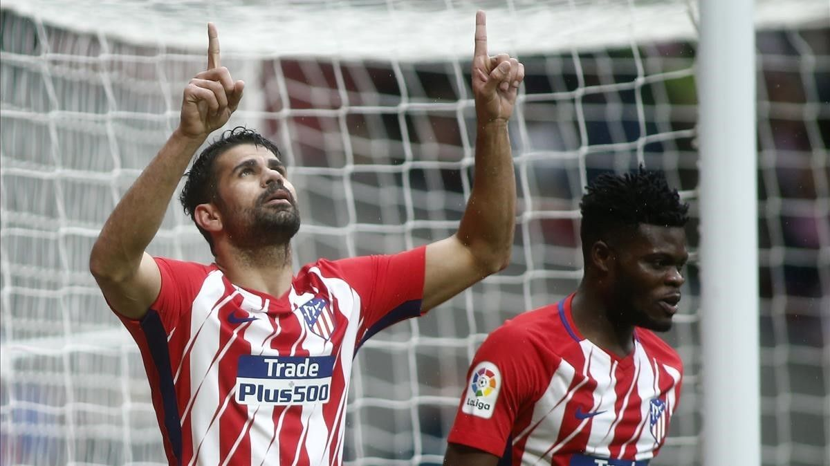 Diego Costa celebra un gol con el Atlético señalando al cielo.