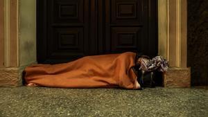 Un hombre duerme en las escaleras de una iglesia de l'Hospitalet de Llobregat.
