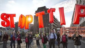 Unos manifestantes portan globos con los que piden que se pare el TTIP, en Bruselas.
