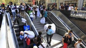 Un grupo de manteros entra en el metro huyendo de la presión policial en la Rambla, estejueves.