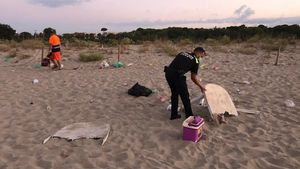 Los servicios de limpieza adecentando la playa deMuntanyans de Torredembarra tras disolver un botellón.