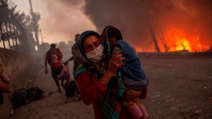Una mujer huye con su hijo del incendio declarado en el campo de refugiados de Moria, el 9 de septiembre del 2020.