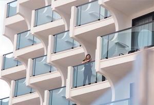 Una turista en el balcón de un hotel en la playa de Palma.