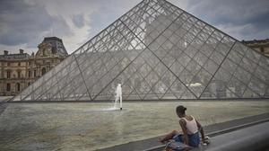 Una mujer se refresca junto a la Pirámide del Louvre, desierta de gente.