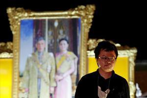 Anon Nampa, uno de los líderes de las protestas antigubernamentales, posa ante una foto de los reyes de Tailandia.