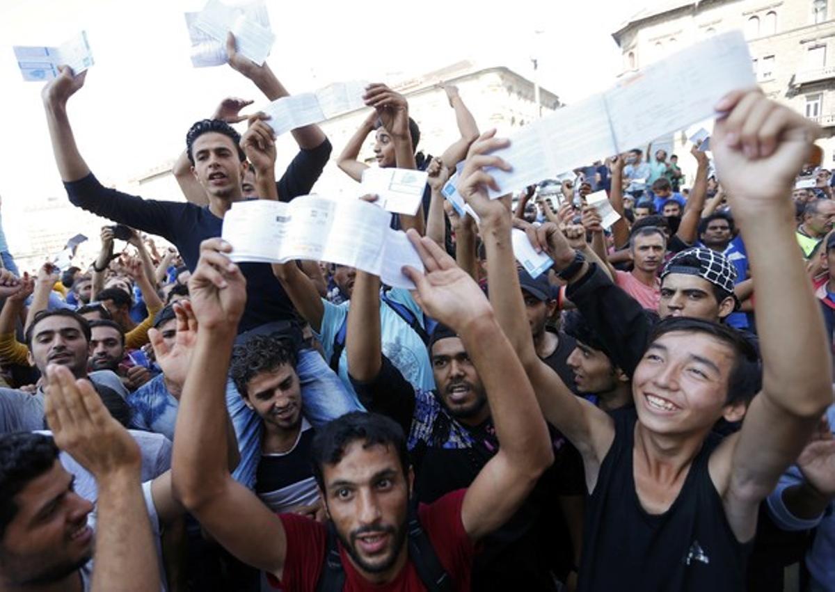Los refugiados muestran sus billetes de tren con indignación mientras esperan que los trenes vuelvan a circular en la estación de Keleti.