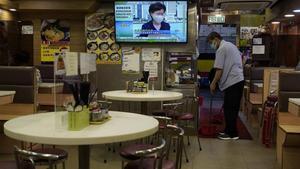 Un empleado de un restaurante limpia el local mientras la jefe del ejecutivo de Hong Kong,Carrie Lam, anuncia por televisión el aplazamientode las elecciones.