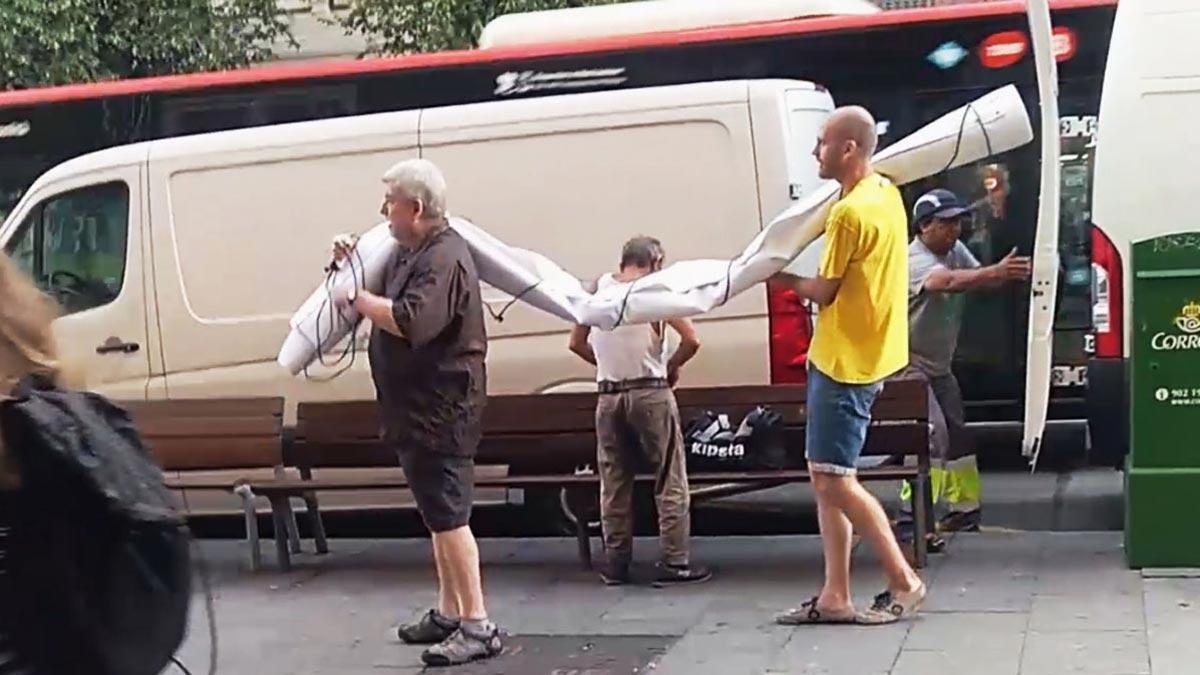 Unos hombres sacan de una furgoneta la pancarta supuestamente contraria al Rey.