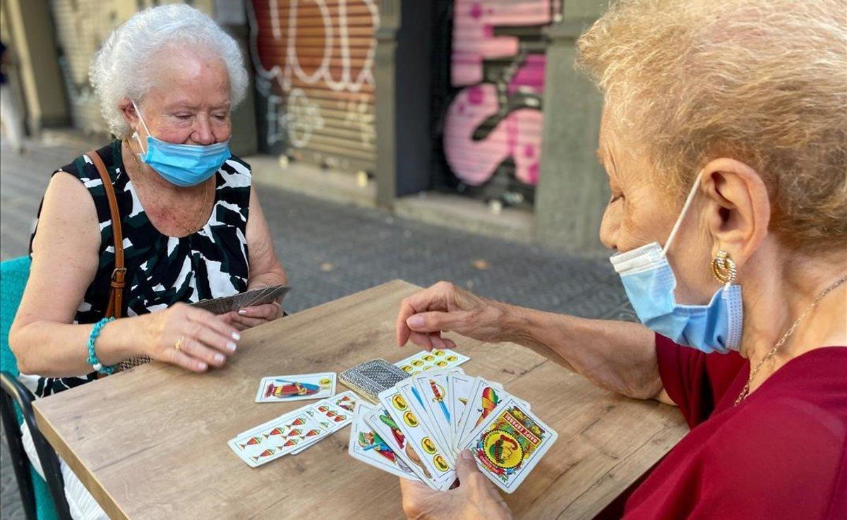 Dos mujeres con mascarilla juegan a las cartas en la calle, en el barrio del Eixample de Barcelona.