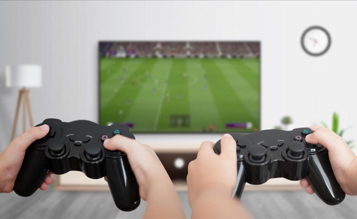 Unos chicos juegan con una consola de videojuegos.