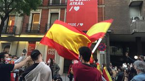 Un grupo de personas se manifiestan ante la sede del PSOE, protegida por la Policía Nacional, por la gestión de la crisis sanitaria, este domingo 17 de mayo.