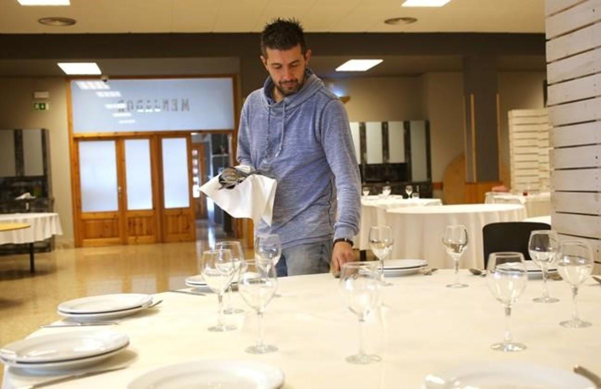 Josep Badia prepara las mesas del restaurante Can Quico de Prats de Lluçanès.