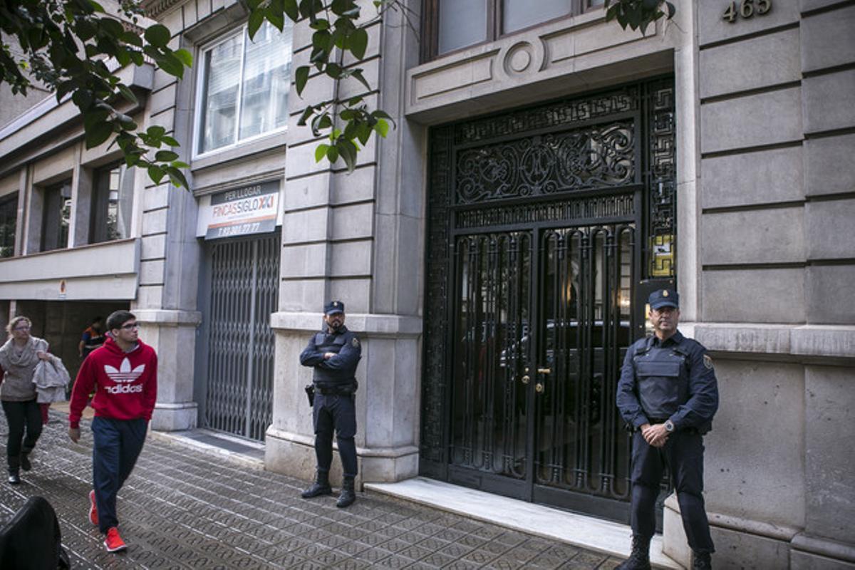 Dos agentes de la Policía Nacional custodian el portal del domicilio de Mercè Gironés, exmujer de Jordi Pujol Ferrusola, que está siendo registrado.