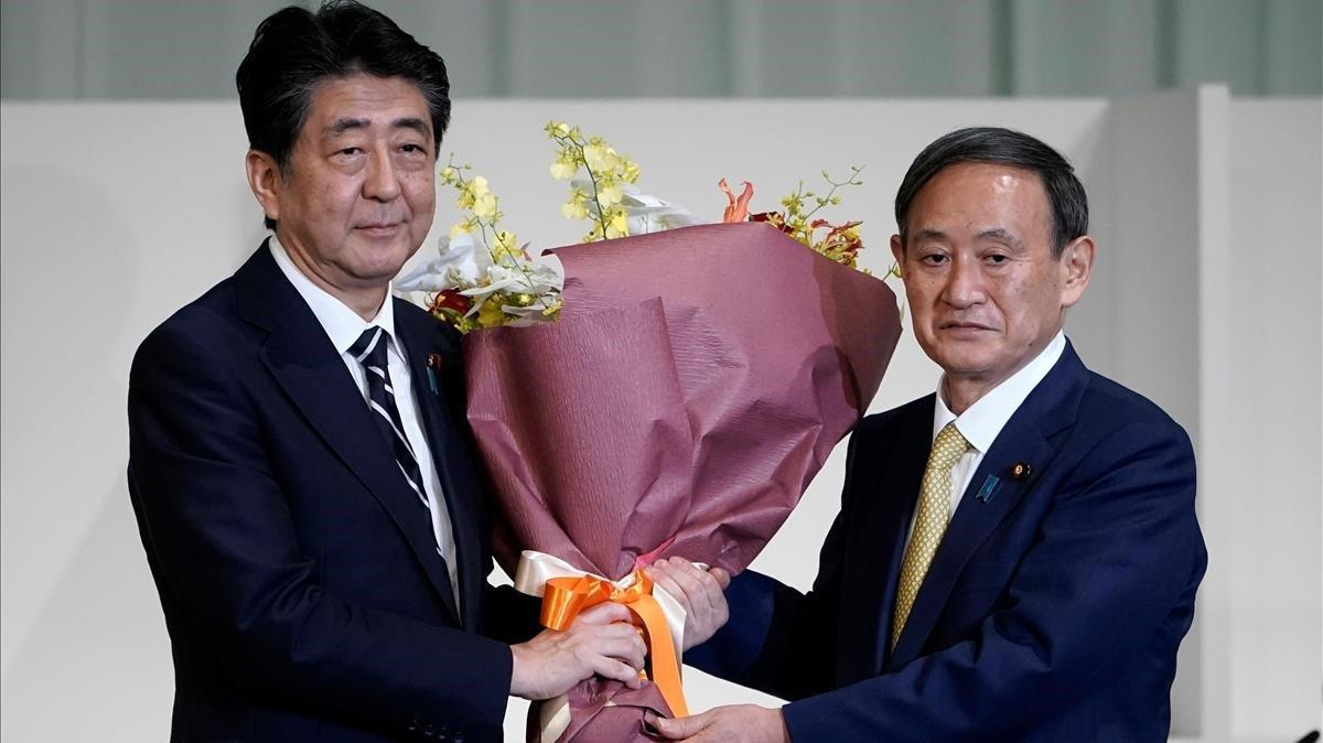 Suga (derecha) recibe un ramo de flores tras convertirse en el lider del partido gubernamental de Japón.