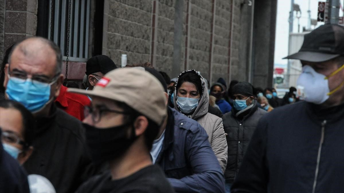 Un grupo de personas hace cola en Nueva York para ayuda social.