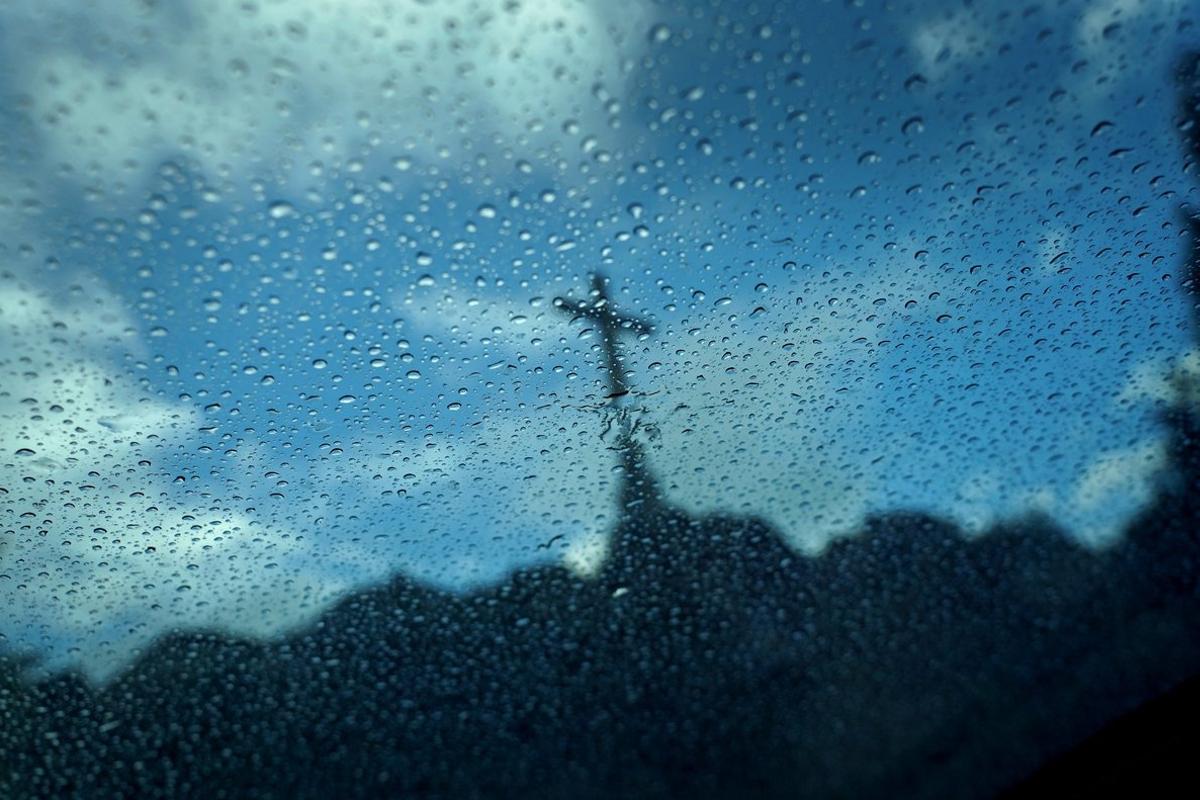 La cruz del Valle de los Caídos empañada por las gotas de la lluvia.