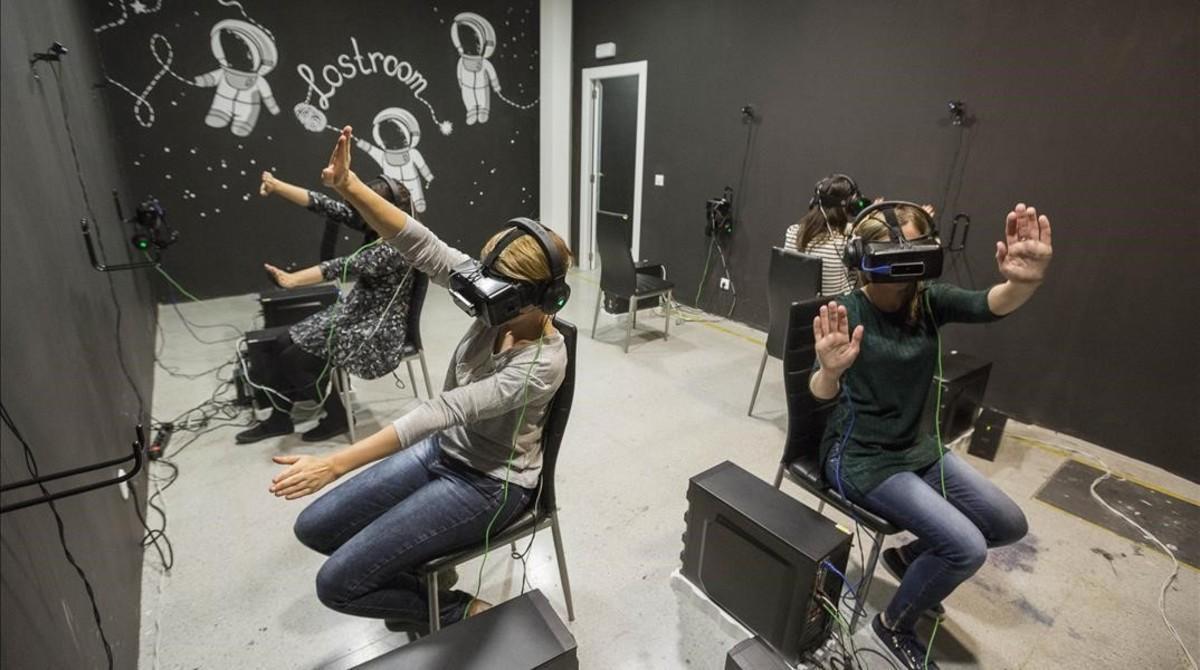 Cuatro jugadoras de 'Cosmos', el 'escape room' virtual deLostroom, intentan volar sin despegar los pies del suelo. Lo que ellas estánviendo: que son una pandade 'cyborgs' en una estación espacial.