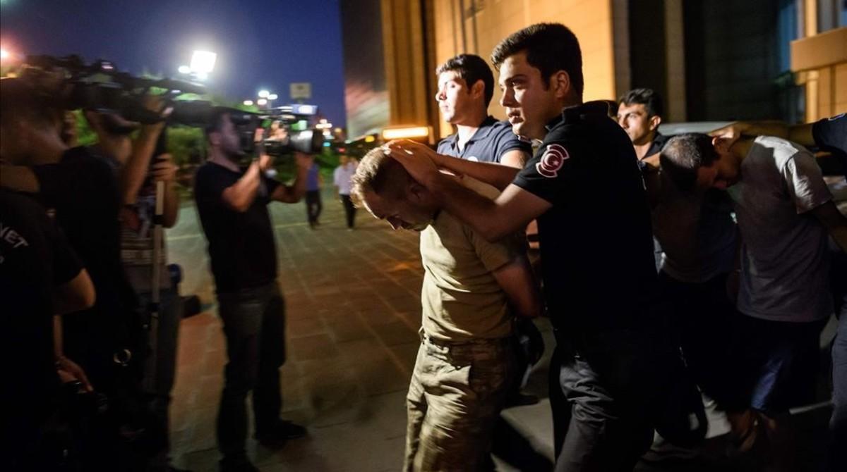 Agentes antidisturbios escoltan a soldados turcos supuestamente implicados en la intentona golpista, en Estambul.