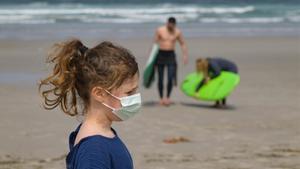 Una niña con mascarilla en una playa de A Coruña, el 3 de abril.