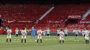 Jugadores del Sevilla y el Betis guardan un minuto de silencio.