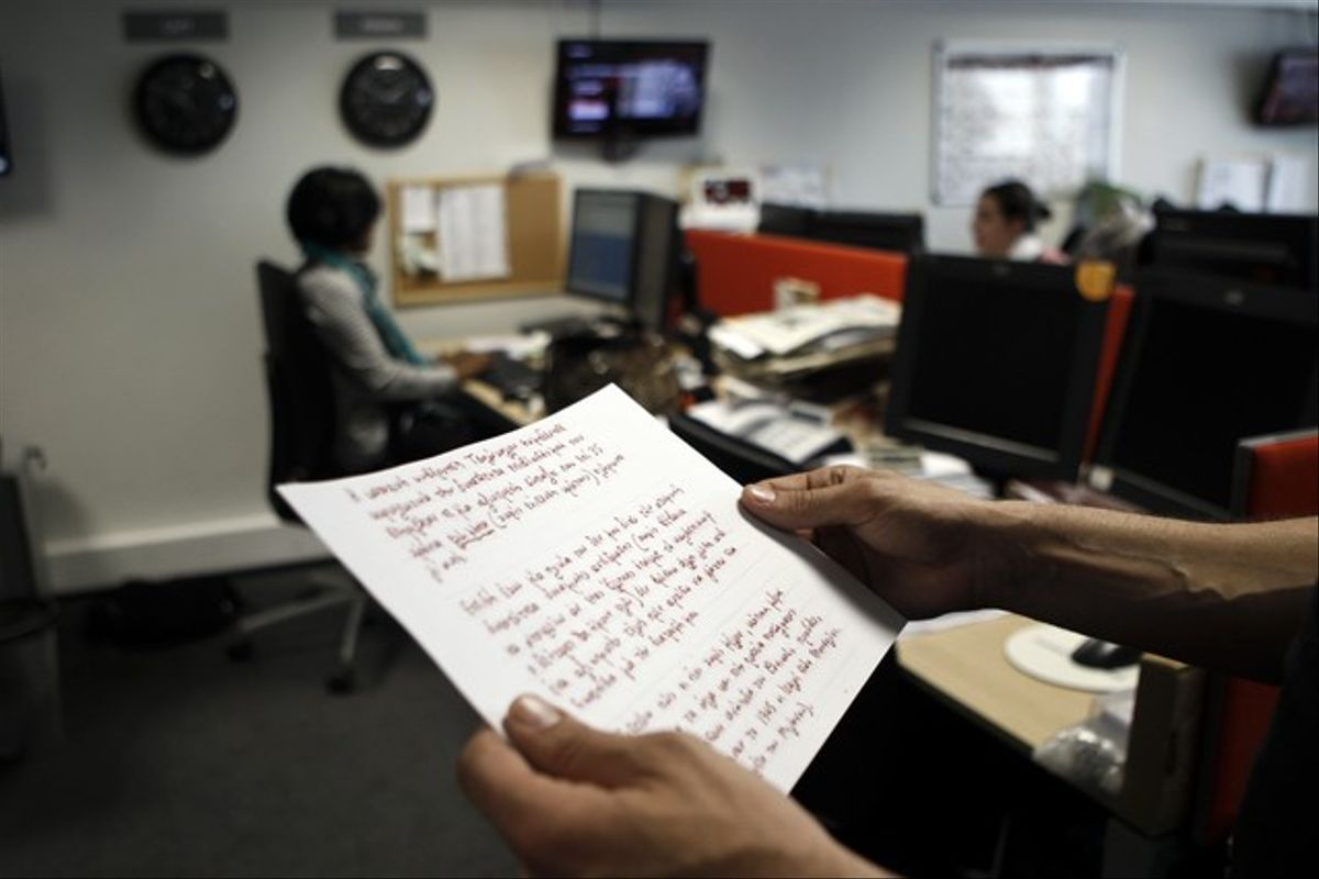 Un periodista de la agencia Reuters lee en Atenas una copia de la nota de suicidio del jubilado griego.