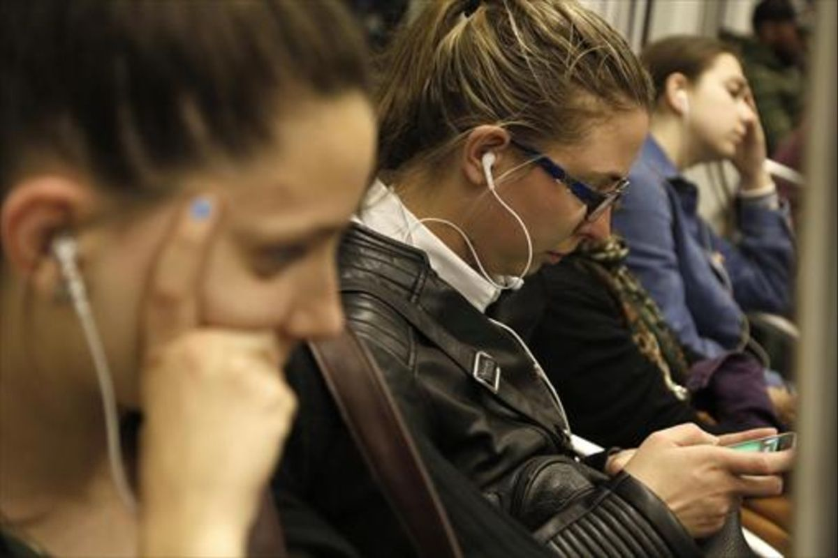 Jóvenes escuchando música con auriculares en el metro.