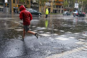 Un hombre cruza corriendo la avenida Diagonal.