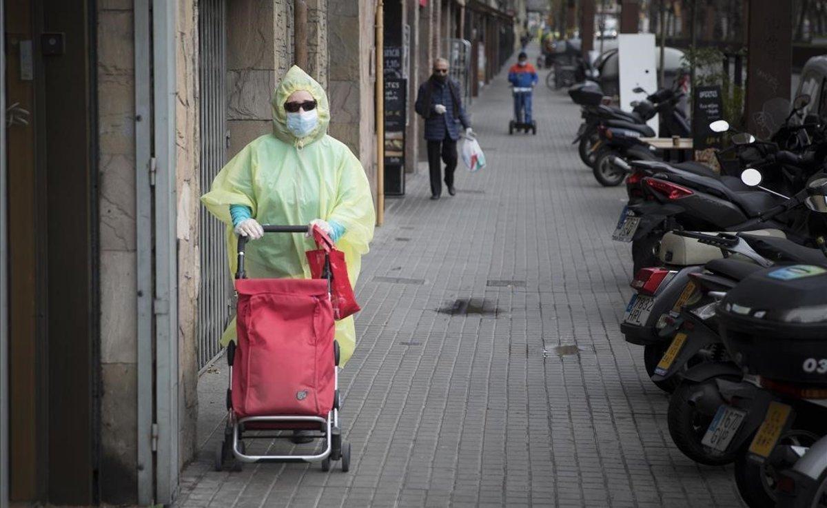 Una mujer sale a comprar por Barcelona totalmente protegida para prevenir el contagio por coronavirus.