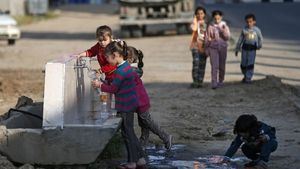 Niños palestinos llenan botellas de agua en una fuente en el campo de refugiados de Khan Yunis, al sur de Gaza, el pasado día 11.