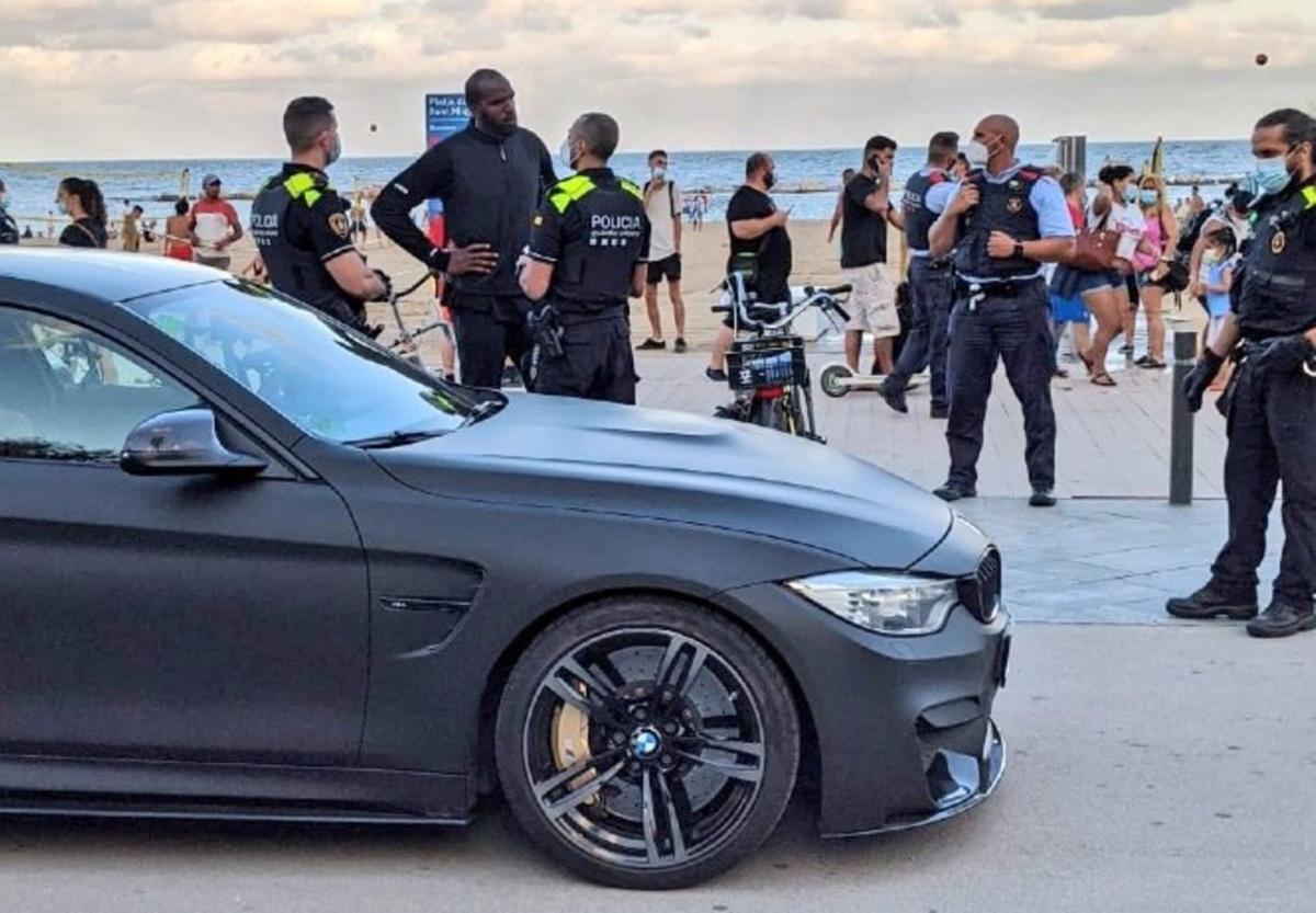 Los agentes le explican a Samardo Samuels que no puede ir con su BMW por el paseo marítimo de Barcelona.