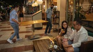 Unos camareros retiran mesas en un local de Platja d'Aro, el viernes por la noche.
