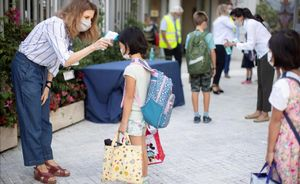 Una trabajadora toma la temperatura a una niña a la entrada de un colegio en Esplugues de Llobregat.