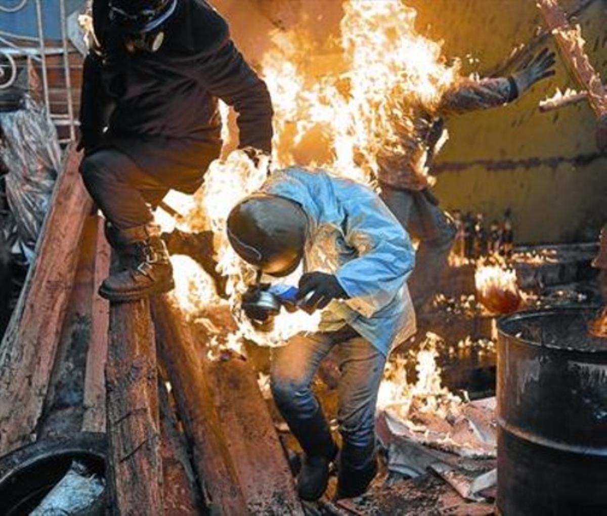 Algunos activistas son alcanzados por las llamas en las barricadas.