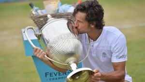 Feli López besa el trofeo de campeón en Queen's.
