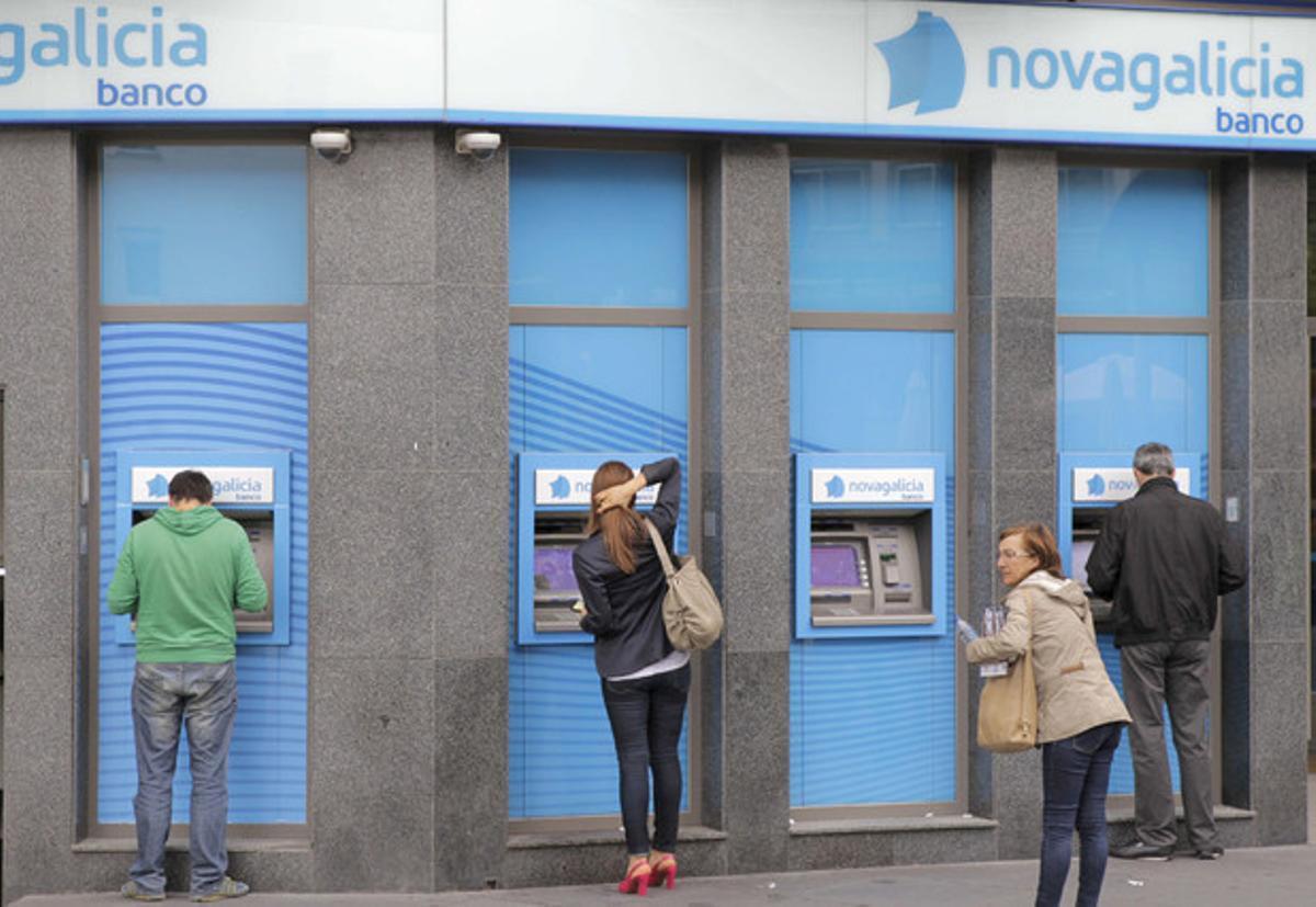 Varios usuarios en cajeros de una sucursal de Novagalicia Banco, en Santiago de Compostela.