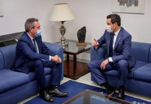 El alcalde de Sevilla y próximo candidato socialista a la Junta, Juan Espadas (i), conversa con el presidente andaluz, Juanma Moreno (d), durante su primer encuentro tras las primarias del PSOE-A, este 24 de junio en el Parlamento autonómico.