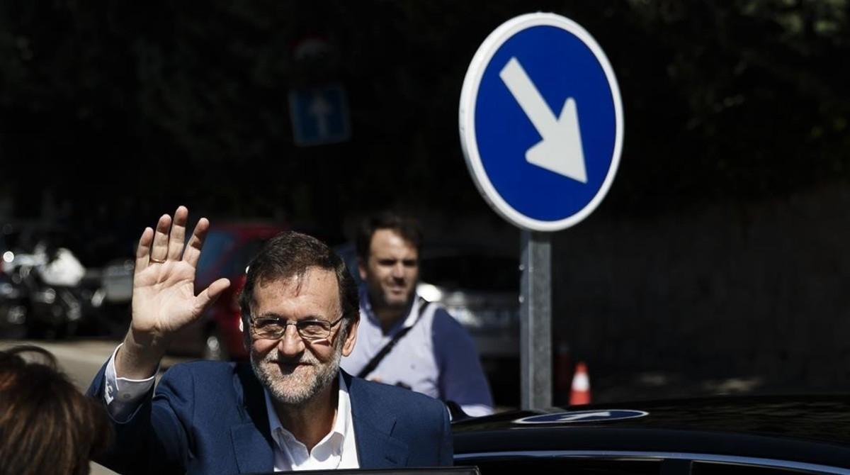 Rajoy saluda tras ir a votar, este domingo en Madrid.