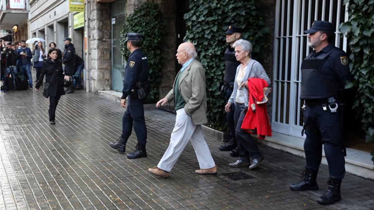 Jordi Pujol y Marta Ferrusola abandonan su domicilio durante el registro policial.