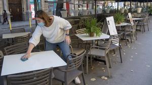Una mujer repasa las mesas de una terraza en Rambla de Catalunya.