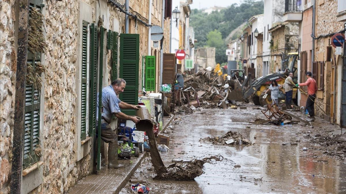 Vecinos de la localidad mallorquina de San Llorenc tratande quitar el barro y el agua acumulados en las casas y lascalles a causa de las inundaciones del martes.