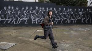 Teo Vázquez, muralista de gran formato, junto a su obra de 20 metros en el patio interior de la cooperativa de viviendas de Bac de Roda.