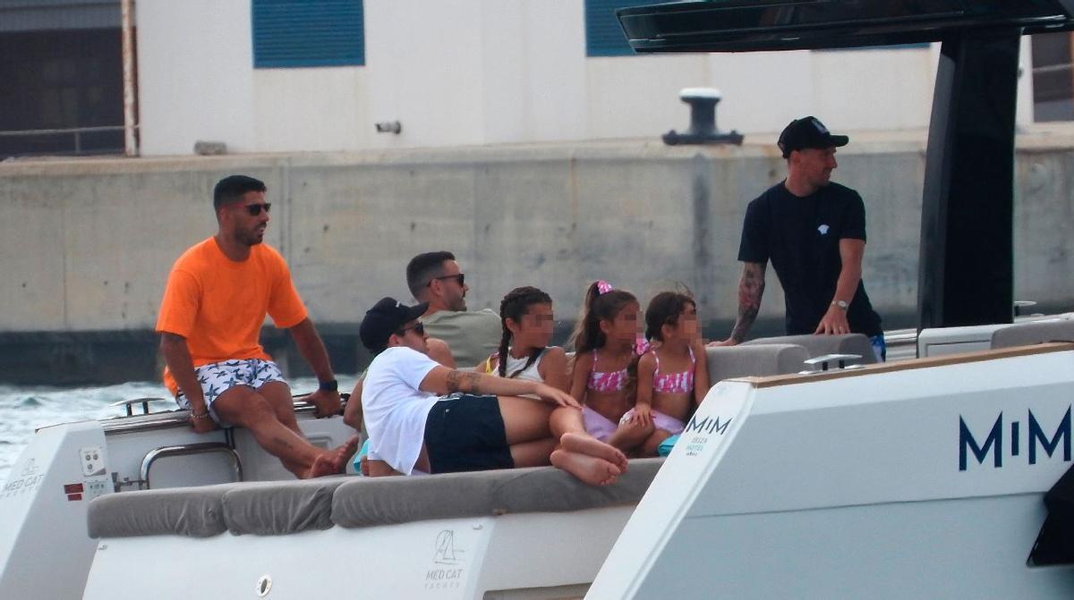 Luis Suárez (izquierda, de naranja), Cesc y Messi (derecha del todo) navegan por aguas de Eivissa con sus familias, este viernes.