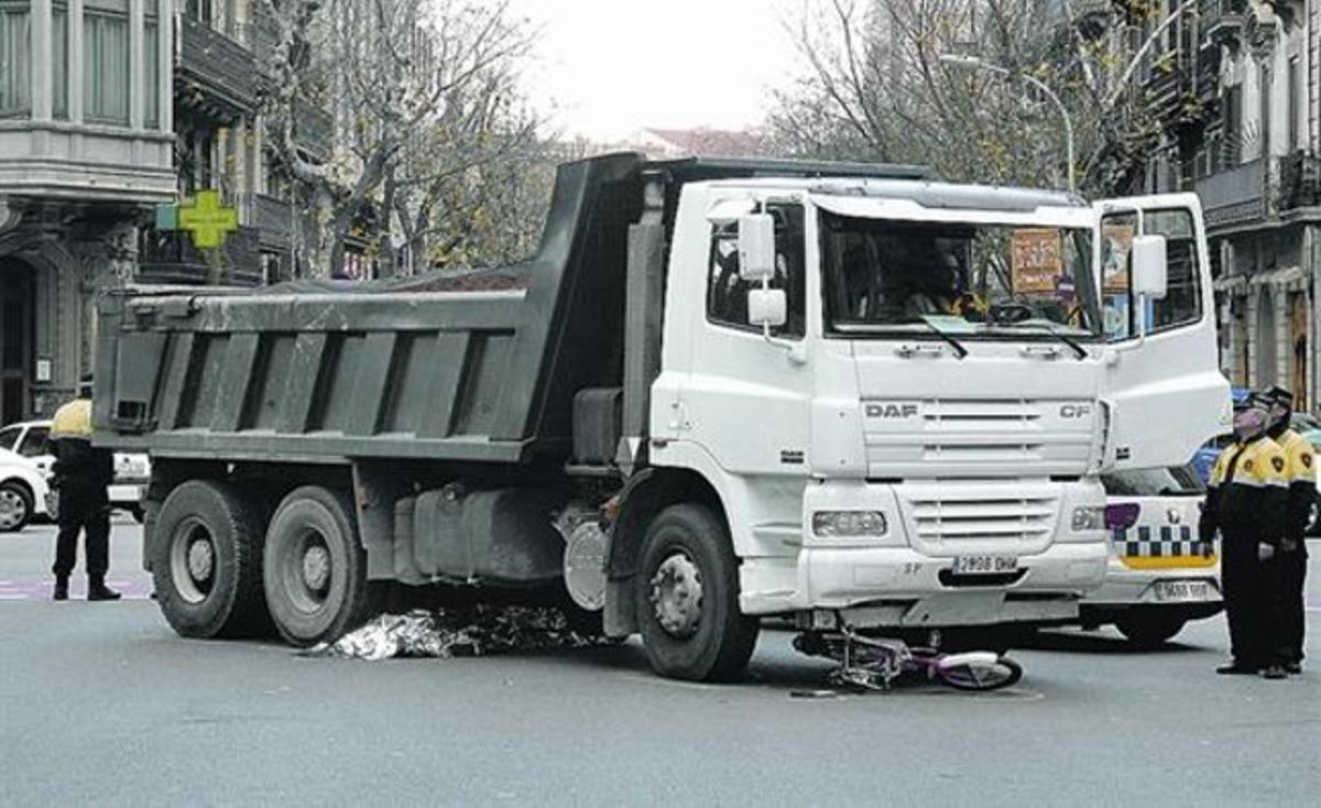 El cuerpo de la fallecida y su bicicleta, bajo el camión que causó el atropello, ayer.