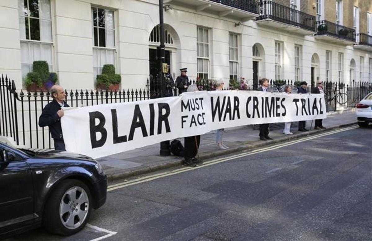 Manifestantes frente a la casa de Tony Blair con la pancarta Blair debe hacer frente a un juicio por crímenes de guerra.