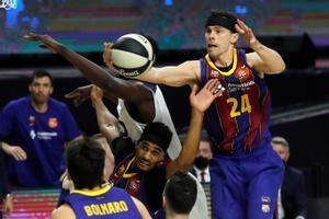 El azulgrana Kuric se eleva por encima de un grupo de jugadores para capturar un rebote