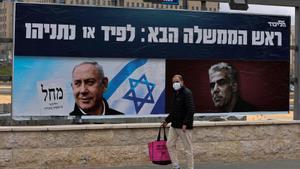 Un israelí camina frente a los carteles electorales del primer ministro, Binyamin Netanyahu, y uno de sus oponentes, Yair Lapid, líder del partido Hay Futuro.