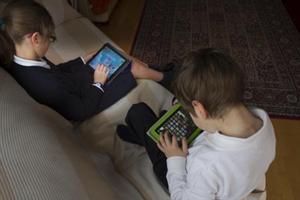 Dos niños juegan con tabletas electrónicas.