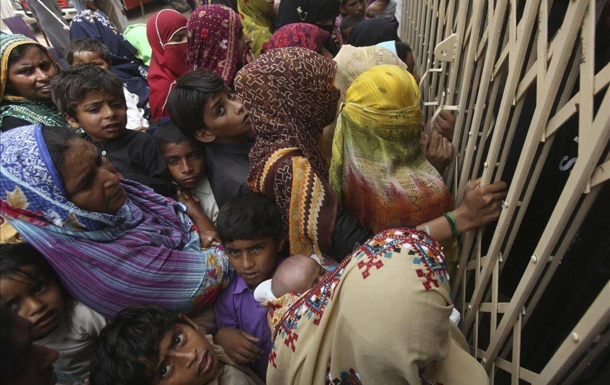 Familias paquistanís esperan en la entrada de un hospital para realizarse las pruebas de VIH.